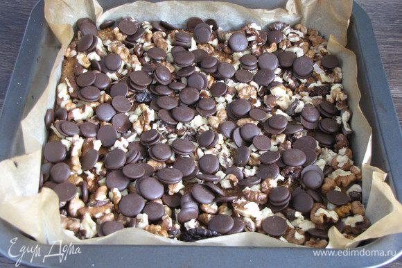 Шоколад порубить мелко, а орехи крупно. Я использовала готовые шоколадные кружочки. Посыпать готовый корж шоколадом и орехами.
