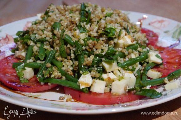 Помидор нарезать тонкими кружками поперек, выложить на тарелку в один слой, сбрызнуть оставшимся оливковым маслом, посолить и поперчить, в центр выложить салат.