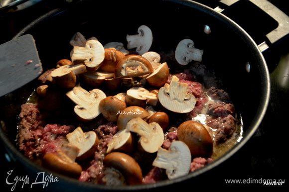 Добавить очищенные и порезанные грибы, мелко порубленный чеснок. Обжаривать, помешивая, 8 мин.