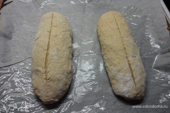 Из подошедшего теста сформируйте два батона, выложите на противень, выстланный бумагой для выпечки. На батонах сделайте надрезы. Дайте еще подойти.