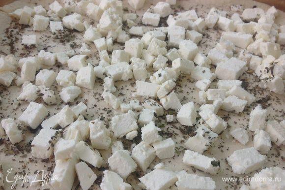 Тесто хорошо поднялось, смазываем доску оливковыми маслом (немного) и раскатываем корж толщиной 0,5 см, из этого количества теста выходит 2 коржа 25*30 см или один большой корж на весь стандартный противень, посыпаем корж густо (!) сухим базиликом, поверх выкладываем порезанную соленую брынзу.