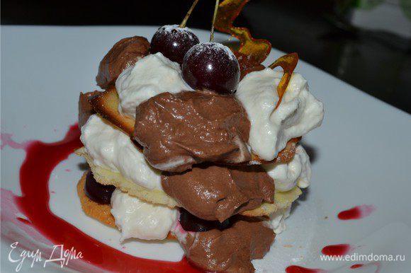 Начинаем собирать наш десерт. Выкладываем бисквит основу. На него с помощью ложки по очереди выкладываем крем с темным и белым шоколадом. Затем добавляем свежую вишню разрезанную пополам, без косточки. Накрываем еще одним пластом и все повторяем. Можно сделать не 3 слоя а больше. Как вам нравится. Сверху десерт украшаем карамелью и ягодами вишни. Подаем с вишневым топпингом. Приятного аппетита!