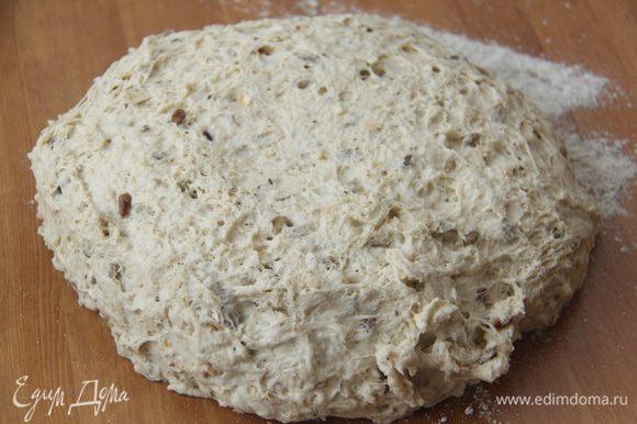 Через 2 часа выложить тесто на присыпанный мукой стол, обмять, сформировать батон, обвалять в ржаной или пшеничной цельнозерновой муке. Оставить на расстойку на 1 час, прикрыв полотенцем.