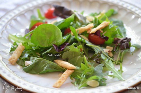Салат разложить по тарелкам. Помидоры черри на 2 части разрезать. разложить. Посыпать миндальными пластинками по желанию, чипсами или подсушенной питой, поломанной на кусочки.