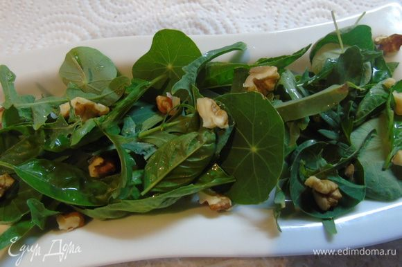 Выложить зелень, посыпать орехами и полить заправкой.