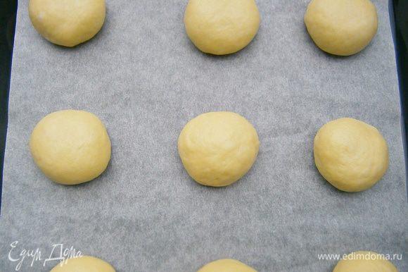 Подошедшее тесто обмять и разделить на 10 частей. Каждую часть скатать в шарик. Уложить на противень, застелив бумагой для выпечки.
