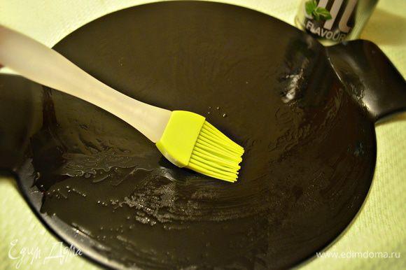Духовку включить на 220 С. Форму для пиццы немного смазать оливковым маслом (у меня специальная форма для пиццы d=26 см) и выложить на неё тесто, слегка обмять и придать форму круга. Накрыть полотенцем и отставить на 10 минут.