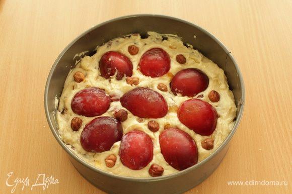 Выложите тесто в разъемную форму диаметром 20 см. Разрежьте пополам отложенные в сторону сливы, удалите косточки и выложите на пирог. Посыпьте пирог лесным орехом и слегка вдавите их в тесто.