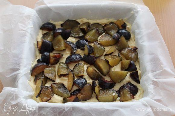 Выложить форму бумагой для выпечки, на нее выложить тесто (тесто получается довольно густое), поверх - порезанные сливы.