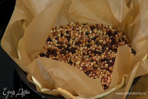 Накрыть тесто вторым листом для выпечки, насыпать сверху горох или фасоль и отправить в разогретую духовку на 10‒12 минут.