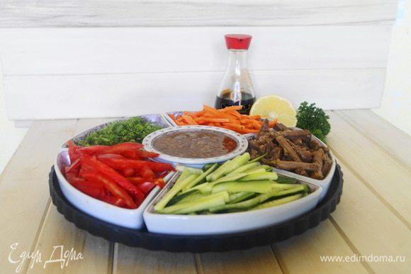 В чашу, в которой будем подавать блюдо, в центре устанавливаем соусник, по кругу выкладываем небольшими горками овощи и мясо. Подаем к столу. Каждый может взять себе в тарелку те составляющие, которые ему больше всего нравятся, или положить каждого ингредиента понемногу, заправить соусом и перемешать. Приятного аппетита!