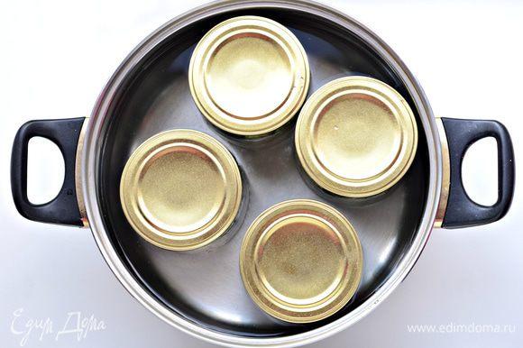 Прикрыть банки стерилизованными крышками. Простерилизовать (с момента закипания воды) 5 минут - 0,5 литровые банки, 7 минут - 700 гр.