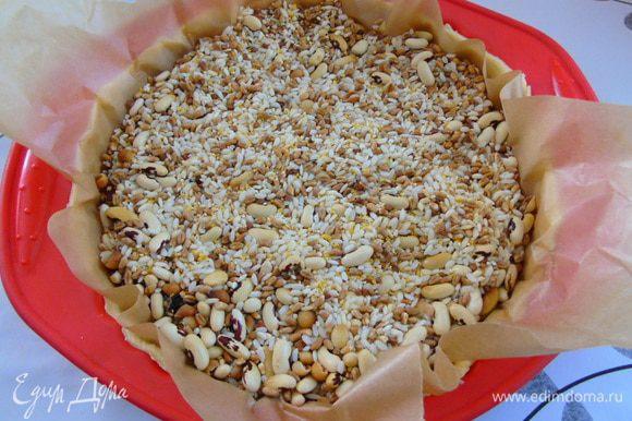 Выложить в форму и сформировать бортик. Накрыть пергаментом и насыпать сверху груз (фасоль,горох и т.д.) Отправить в разогретую до 180С духовку на 10-12 минут.