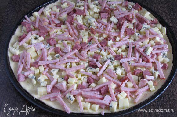 Посыпать сначала моцареллой, затем горгонзолой. Сверху равномерно распределить ветчину. Выпекать пиццу в духовке, разогретой до 220 град., пока сыр не растопится полностью и только начнет подрумяниваться.
