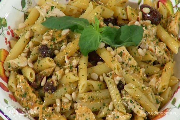 Переложить макароны с курицей и соусом на блюдо, посыпать оставшимися орехами, сбрызнуть оливковым маслом и украсить базиликом.