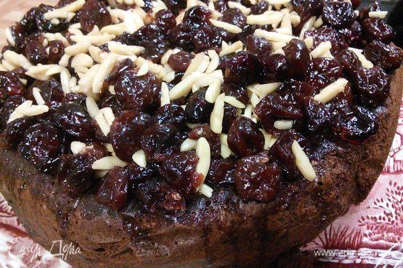 Длинной палочкой проколите дырочки и пропитайте глазурью весь торт. В конце выложите на торт вишню и миндаль.