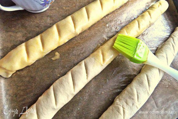 Раскладываем заготовки на смазанный маслом пергамент на противне. Делаем надсечки ножом,смазываем взбитым яйцом кисточкой.