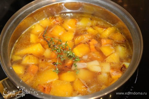 Переложите тыкву в кастрюлю, добавьте к ней картофель, тимьян и влейте овощной бульон. Доведите до кипения и варите 15-20 минут, пока картофель не станет мягким.