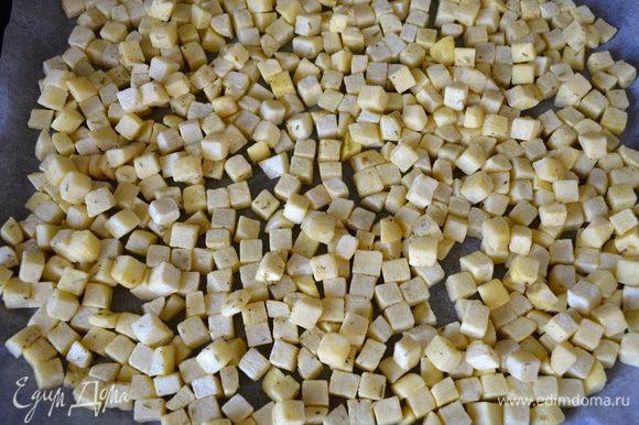 Выложить картофель в один слой на противень, застеленный пекарской бумагой.