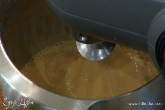 В чашу комбайна влить молоко, добавить 1 1/2 банки вареного сгущенного молока и взбить все насадкой-венчиком в густую карамельную массу.