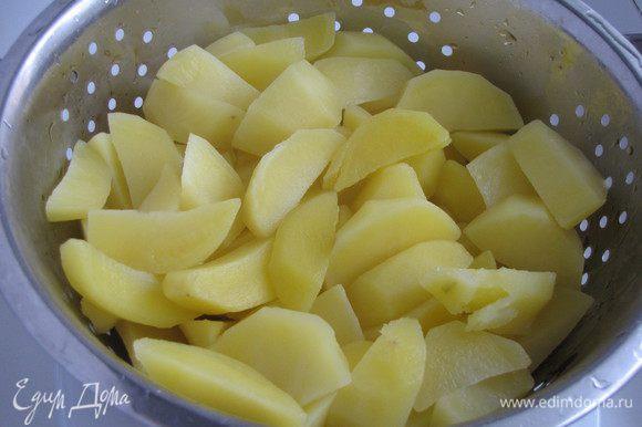 Нарезать дольками. Вскипятить воду, выложить картофель и варить ровно две минуты после закипания. Картофель откинуть на дуршлаг и промыть холодной водой.