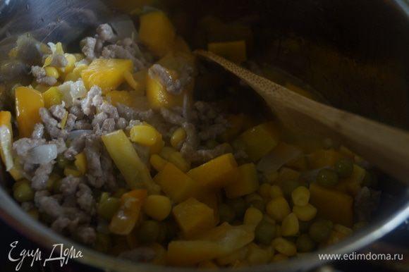 Добавляем к фаршу обжаренные овощи с тыквой, зеленый горошек и кукурузу. Заливаем овощным бульоном. Солим, перчим и перемешиваем. Готовим еще около 20-25 минут.