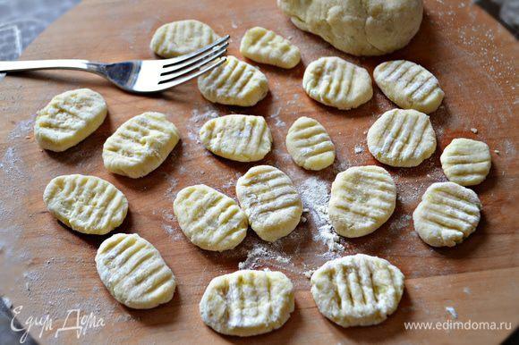 Пюре слегка остудите, добавьте половину муки и перемешайте. Затем выложите на рабочую поверхность присыпанную мукой, замешивайте тесто, оно не должно быть слишком мягким, иначе ньокки развалятся при варке. Из полученного теста сформируйте колбаски диаметром 1,5 см и разрежьте на кусочки по 2 см. Обваляйте слегка в муке и прижмите вилкой с обеих сторон. Отварите ньокки в кипящей подсоленной воде в течение 2 минут. Готовые ньокки выложите на тарелку и добавьте немного масла, чтобы они не склеивались друг с другом.