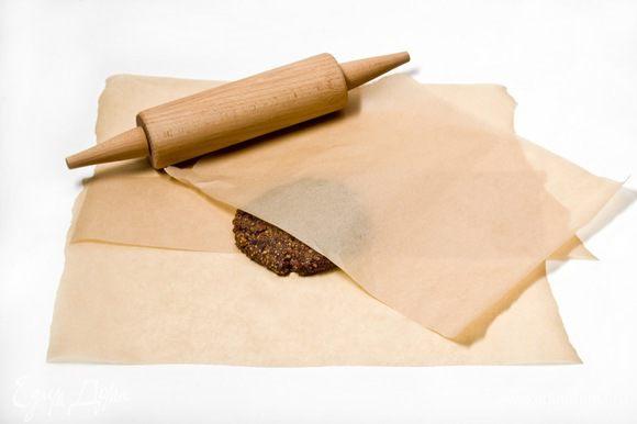 Выложить ореховую смесь между двумя листами пергаментной бумаги и раскатать пласт теста, толщиной 1,5 см.