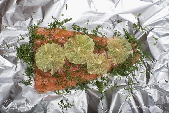 Филе лосося нарезать на порционные куски, посолить и полить соком 2/3 лайма. Поставить на 20 минут в холодильник. Выложить куски рыбы на фольгу, посыпать укропом. Лайм очистить, нарезать кружочками и выложить на филе рыбы. Сверху все сбрызнуть оливковым маслом, накрыть фольгой и поставить в разогретую до 180°C духовку на 15-20 минут.
