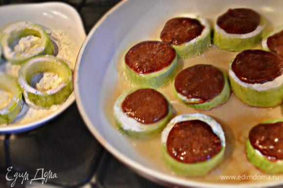 Кабачковые кольца слегка обваляйте в муке, выложите в сковороду с разогретым растительным маслом. С помощью ложки внутрь кольца выкладывайте печеночную массу. Обжаривайте на среднем огне с двух сторон до готовности.