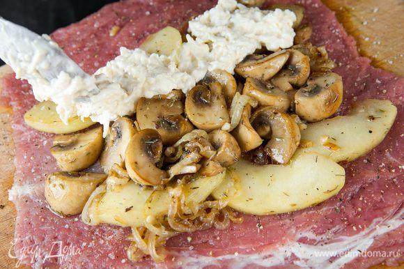 Равномерно распределяем начинку из овощей и грибов по мясу, сверху кладем сметанно-сырную смесь.
