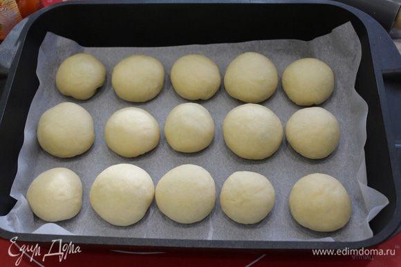 Форму для выпечки выложить пекарской бумагой, расположить булочки, оставляя расстояние между ними.