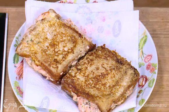 Сэндвичи окунуть в молочно-яичную смесь, так чтобы весь хлеб полностью пропитался, выложить на сковороду и обжарить с обеих сторон до золотистой корочки, затем переложить на бумажное полотенце, чтобы удалить излишки жира.