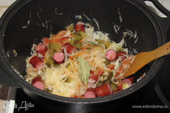 За 15-20 минут до готовности капусты, добавить томатную пасту, нарезанный соленый огурец и охотничьи колбаски. Перемешать.