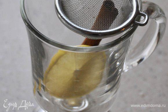 В бокал добавить большую дольку лимона и сахар. Через ситечко процедить глинтвейн. Размешать. Положить палочку корицы из кастрюльки.