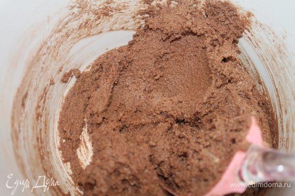 В масляную смесь частями всыпать сухие ингредиенты и смешать лопаткой. Добавить шоколад. и перемешать. Форму 20 см смазать маслом, выложить тесто.
