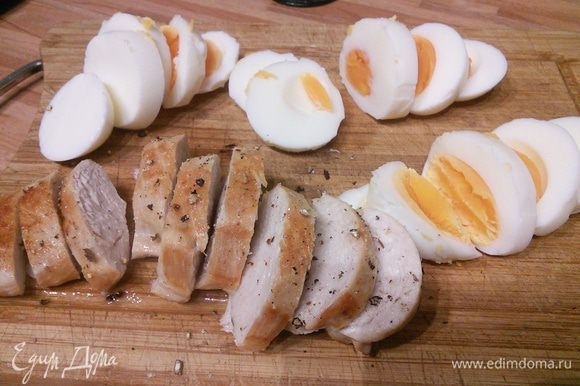 Куриное филе вымыть, обсушить и обжарить на 2 ложках разогретого масла на каждой стороне по 4–5 минут до золотистой корочки. Мясо переложить в тарелку, посолить и поперчить, нарезать ломтиками. Сварить яйца вкрутую, обдать холодной водой, очистить от скорлупы, нарезать кружочками.