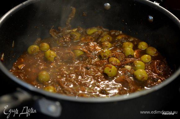 Разогреть оливковое масло на сковороде, обжарить мелко порубленный лук, мелко порезанный зеленый лук, чеснок. Помешиваем и готовим 2-3 мин. Добавить все сухие специи. Готовить 1 мин. Добавить томатную пасту, оливки, изюм, воду.