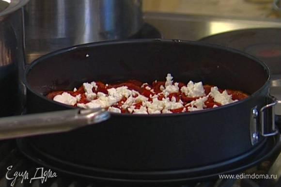 Форму с помидорами вынуть, слегка остудить, сверху уложить поломанную на кусочки фету.
