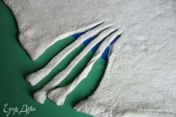 Посыпать поверхность немного мукой. Раскатать скалкой пласт овальной формы. С одного края сделать три глубоких разреза.