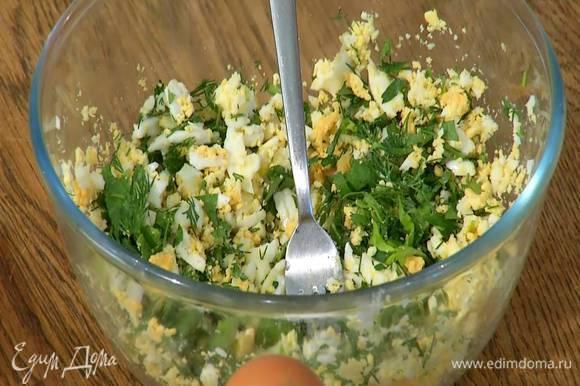 К размятым яйцам добавить половину измельченной зелени, посолить, поперчить и все перемешать.