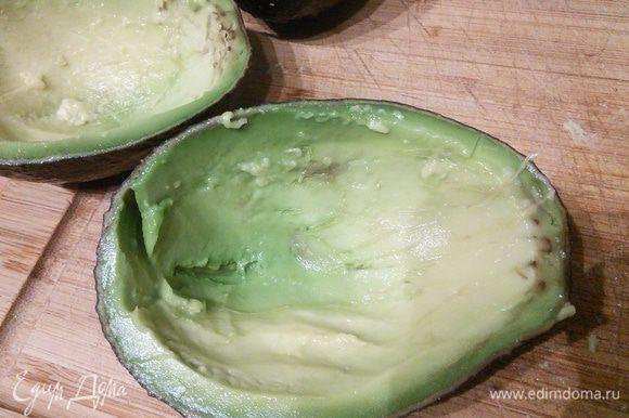 Авокадо вымыть, обсушить, разрезать наполовину, извлечь косточку. Авокадо должен быть спелым. Ложкой вынуть до 2/3 мякоти. Мякоть нарезать и аккуратно вмешать в остальной салат.