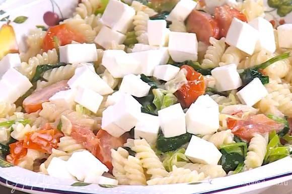 К пасте с помидорами добавить базилик, все перемешать, сверху выложить фету.
