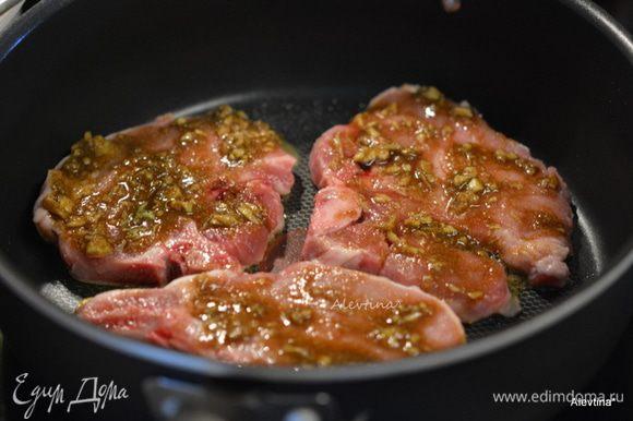Разогреть сковороду с оливковым маслом 2 ст.л. Свиные котлеты смазать с 2х сторон приготовленной пастой. Обжарить с обеих сторон на среднем-медленном огне до готовности.