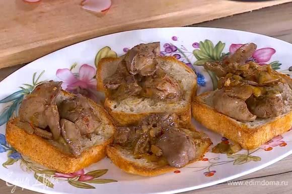 На обжаренные тосты вложить куриную печень с луком и чесноком и полить соусом, который выделился при жарке.