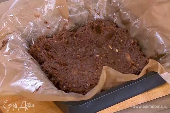 Небольшую форму для выпечки выстелить бумагой, смазанной оставшимся сливочным маслом, выложить тесто и разровнять его.