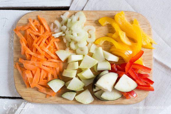 Разогрейте духовку до 200°C. Крупно нарежьте кабачок, баклажан и морковь. Порубите стебли сельдерея и тонко нарежьте красный и желтый перец.