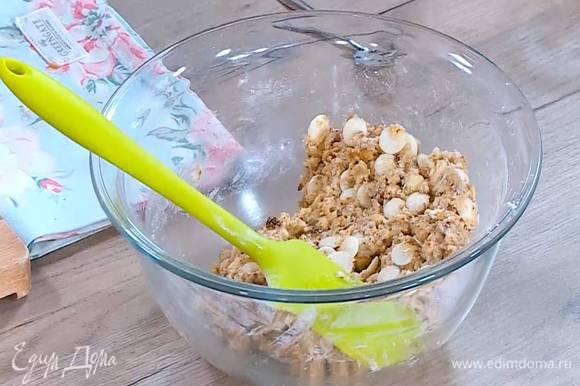 К муке добавить сахарно-яичную массу, измельченные орехи, белый шоколад, кокосовую стружку и вымешать тесто.