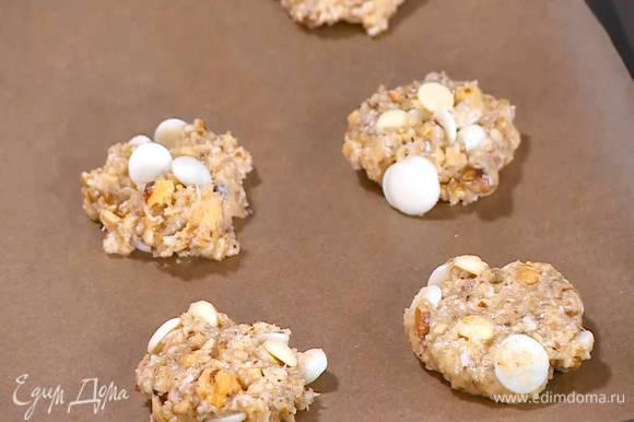 Сформировать из теста небольшие лепешки и выложить на противень, выстеленный бумагой для выпечки.
