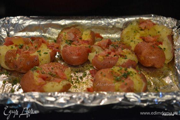 Картофель сбрызнуть оливковым маслом. Посыпать сверху чесночным порошком, солью и черным перцем по вкусу, беконом и шнит-луком колечками. Поставить в духовку на 20-25 мин. Или в гриль с крышкой.